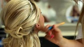 perfection : Young girl sitting on a char during makeup process Stock Footage