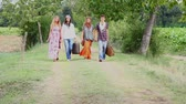 embraced : Hippie Group Walking on a Countryside Road