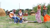 évjárat : Hippie Group Playing Music and Dancing Outside Stock mozgókép