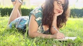 campus : Beautiful Young Woman at Park Writing on Notepad