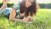 caneta : Beautiful Young Woman at Park Writing on Notepad