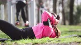 bruneta : Young woman doing abs exercises at park Dostupné videozáznamy
