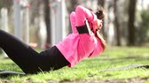 muzyka : Young woman doing abs exercises at park Wideo