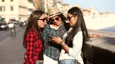 drby : Three young women with smart phone in the city talking and smiling. This is a mixed race group one girl is half asian and one is middle eastern. Lifestyle friendship and urban life concepts.
