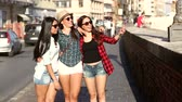 holding : Three happy women walking in the city talking each other and smiling. This is a mixed race group one girl is half asian and one is middle eastern. Lifestyle friendship and urban life concepts.