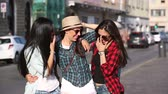 drby : Three happy women walking in the city talking each other and smiling. This is a mixed race group one girl is half asian and one is middle eastern. Lifestyle friendship and urban life concepts.