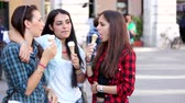 drby : Three happy women eating ice cream in the city talking and smiling. This is a mixed race group one girl is half asian and one is middle eastern. Lifestyle friendship and urban life concepts. Dostupné videozáznamy