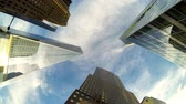 ниже : New York, time-lapse view of skyscrapers and clouds, bottom view. Video taken with a wide-angle lens, with skyscrapers all around and clouds passing over. Blue sky on background. Стоковые видеозаписи