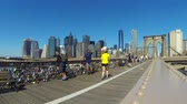 manzara : NEW YORK, USA - AUGUST 26, 2014: Time-lapse of pedestrian and cycle path on Brooklyn bridge in New York, with people walking and cycling. Manhattan downtown skyscrapers on background. Stok Video