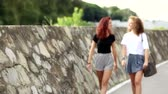 byt : Two girls walking on the footpath, they are friends and seem to be happy. Summer time, early morning. They walk from out of focus to focus. Lifestyle and friendship concepts.