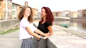 два человека : Two girls talking and laughing together outdoor. They are standing against a small wall with a river and an Italian cityscape on background. Friendship and lifestyle concepts. Стоковые видеозаписи