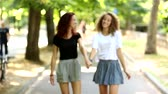 byt : Two beautiful girls walking holding hands at park. They are happy and smiling each other. They could be friends or a couple, lifestyle and friendship concepts. They walk in from out of focus zone.