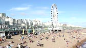 editorial : BRIGHTON, UK  AUGUST 9, 2015: View of Brighton beach with the famous ferris wheel on a sunny day. There are a lot of people on the beach and some of them are also swimming.