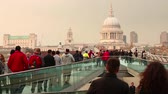 tarihsel : View of St Pauls Cathedral in London with people walking on the Millennium Bridge