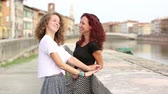 embraced : Two girls talking and laughing together outdoor. They are standing against a small wall with a river and an Italian cityscape on background. Friendship and lifestyle concepts. Stock Footage