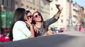 três : Three happy girls taking a selfie in the city. This is a mixed race group, one girl is half asian and one is middle eastern. Lifestyle, friendship and urban life concepts. Stock Footage