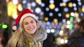eleganckie : Beautiful young woman wearing Santa hat in London. She is blonde, on her early twenties, wearing warm clothes, looking at camera and smiling. On background there are many Christmas lights. Wideo