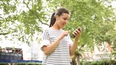 удар : Young woman at park in London wandering and playing with augmented reality game on her smart phone. Blurred people on background. Стоковые видеозаписи