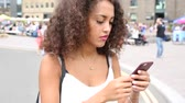 black hair : Young woman in London wandering and playing with augmented reality game on her smart phone. Blurred people on background.