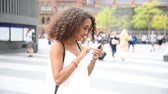 lugar : Young woman in London wandering and playing with augmented reality game on her smart phone. Blurred people on background.