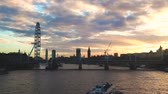 británie : LONDON, UK - January 08, 2016: Panoramic view of London landmarks from Waterloo bridge at sunset with a cloudy sky. London Eye, Big Ben and Golden Jubilee Bridges Dostupné videozáznamy