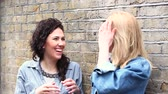 kurtka : Two beautiful women leaning on a wall and talking in London. They are on their mid twenties, one blonde and one brunette, looking each other. Friendship and youth culture concepts. Wideo