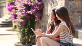 романтический : Two girls looking at a smartphone and sitting on a bench. They are two teen girls on a sunny summer day. Friendship, technologies and lifestyle concepts. Стоковые видеозаписи