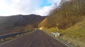 caminho : Car driving a countryside road on a sunny day. Video taken with an action camera from the bottom front of the vehicle. There is a blue sky with clouds, travel and transportation concepts.