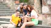 çok : Group of teenagers laughing and looking at a smart phone, bottom view. They are two girls and two boys, they are wearing summer clothes and they seems to be very good friends.