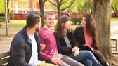 four people : Group of friends having fun at park in Berlin. Mixed race group with caucasian, middle eastern and nordic persons, sitting on a bench and talking. Happiness and friendship concepts.
