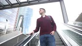 escada rolante : Young man on the escalator. Caucasian boy in the city taking the escalator and looking around. He is carrying a backpack. City life and travel concepts Stock Footage