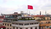 на крыше : Turkish flag over Istanbul rooftops with mosques on background. Flag waving with strong wind in the city of Istanbul. Pan right movement. Стоковые видеозаписи