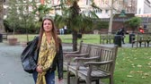 lugar : Young woman walking at park in London. Slow motion video of a girl walking past the camera. Lifestyle and relaxation concepts