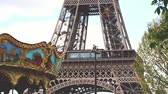 carrossel : Close up view of the Eiffel Tower in Paris. Blurred carousel on the left and some trees on the right of the frame. Hand held video with smooth movement Stock Footage