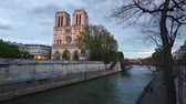 francês : Notre Dame de Paris cathedral at dusk with Seine river on foreground. The facade has some lights on, the sky is cloudy. Travel and architecture concepts.