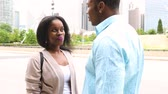 namorado : Happy black couple talking in Chicago. A man and a woman standing face to face and having a nice conversation in the city, laughing and looking each other. Lifestyle and happiness concepts. Vídeos