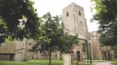 church : Church of St Mary and St Eanswythe in Folkestone, Kent, UK. Trees and tombs on the garden around the church.