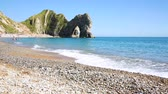 kanál : Beach and rocks in Dorset county, England, UK. People sunbathing and swimming in the clear water. The limestone arch is called Durdle Door. Dostupné videozáznamy