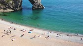 língua : Aerial view of beach and rocks in Dorset county, England, UK. People sunbathing and swimming in the clear water. The limestone arch is called Durdle Door.