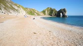 língua : Beach and rocks in Dorset county, England, UK. People sunbathing and swimming in the clear water. The limestone arch is called Durdle Door. Vídeos
