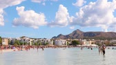 setembro : ALCUDIA, SPAIN - SEPTEMBER 19, 2016: View of a crowded beach in Majorca. Lots of people having fun at seaside, swimming and sunbathing on a sunny summer day. Stock Footage