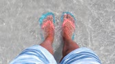 приморский : Male feet on the beach at seaside, high up view. Man wearing flip flops standing on the seashore with water covering the feet. Summer and relax concepts.