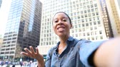 black hair : Black woman having a selfie video call with phone in the city. Adult woman holding her smart phone, looking at camera and talking to a friend, waving her hand and cheering. Technology and lifestyle concepts.