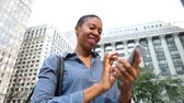 black hair : Black woman typing on the phone in the city with buildings and skyscrapers on background. Smiling adult woman in Chicago, holding her smartphone and sending messages. Lifestyle and technology concepts. Slow motion Stock Footage