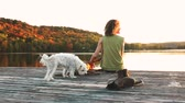 relaxation : Woman and dog relaxing on the dock. Autumn colors, unstaged situation with candid model and her dog. Relaxation and friendship concepts. Stock Footage