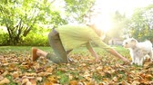 animais : Woman playing with dogs at park or in the backyard. Slow motion video. Autumn colors, unstaged situation with candid model and playful dogs. Lifestyle and friendship concepts.