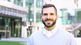 downtown : Portrait of a modern business man, slow motion. Smiling mixed race man with beard looking at camera. Smart casual dressing with shirt and pullover. Contemporary business concept