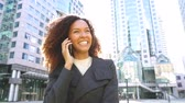 kıvırmak : Modern business woman talking on the phone. Smiling mixed race woman with curly hair looking around. Smart casual dress, backlight in downtown Contemporary business concept Stok Video