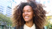 tremer : Curly woman laughing and shaking head, slow motion. Smiling mixed race woman with curls having fun. Smart casual dress. Lifestyle and hairstyle concepts