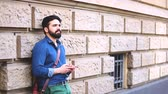 barba : Man typing on smart phone and leaning to a wall. Middle eastern man checking messages and notifications on the phone. City life and communication concepts Stock Footage